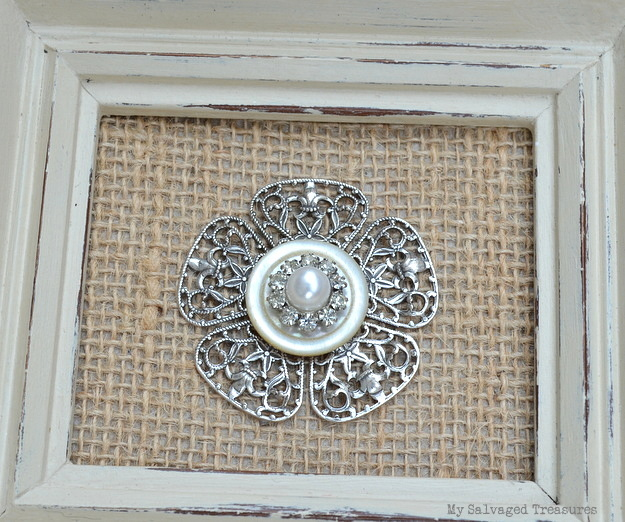framed vintage earring, button, and decorative filigree.