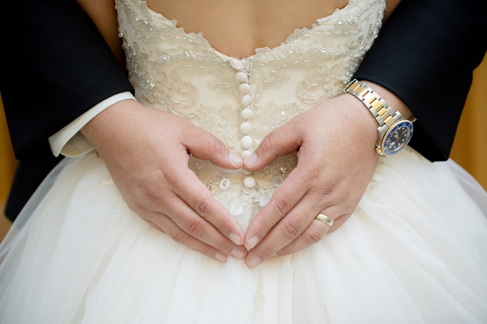 Groom hands in heart shape on bride's dress
