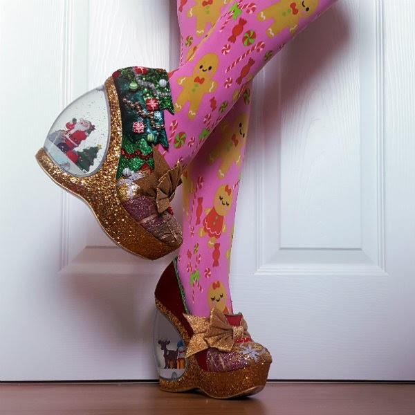 lifted leg showing Santa snowglobe heel of shoe wearing pink gingerbread man tights