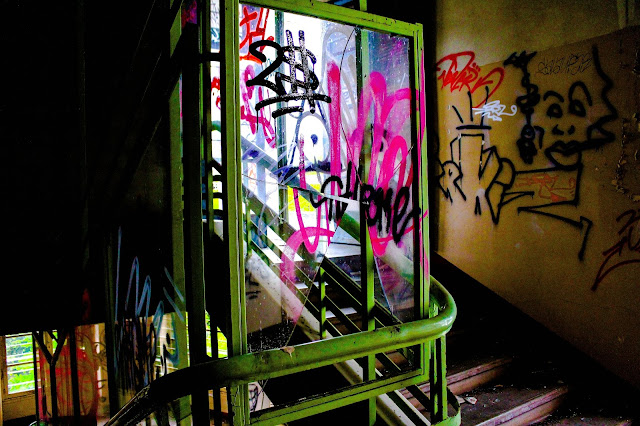 photo de la cage d'escaliers à l interieur du sanatorium avec plein de tags et vitres cassees