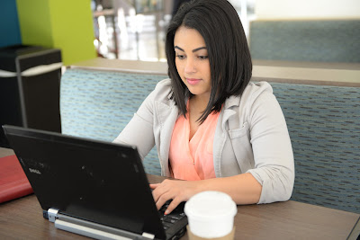 image of student with coffee looking at laptop