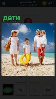 На солнечном берегу женщина в панаме и мужчина ведут детей с кругом купаться и загорать