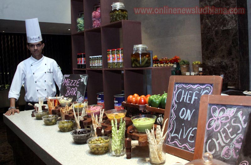 Chef shows Mediterranean food items at Cafe Delish in Radisson Blu