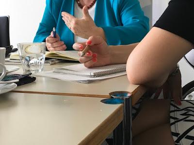 Sprechende Hände einer Dame im bunten Kostümjäckchen, Mitarbeiterin mit roten Fingernägeln