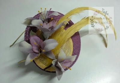 tocado color berenjena y amarillo para boda con ramillete de flores y plumas