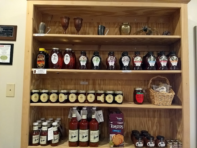Several shelves with honey, syrups and glassware for sale