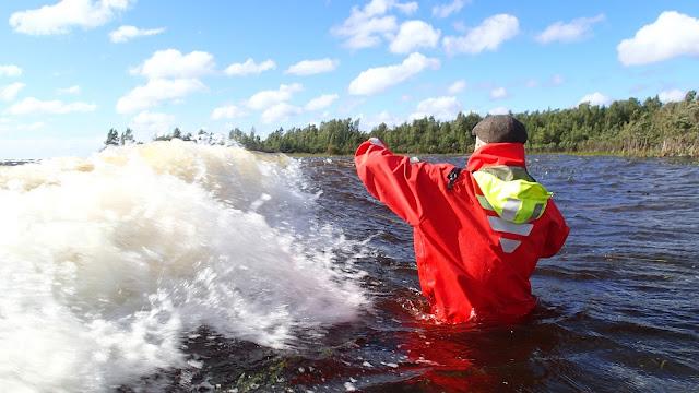 Aalto vyöryy kohti pelastautumispukuun sonnustautunutta miestä, joka seisoo vyötäröä myöten vedessä
