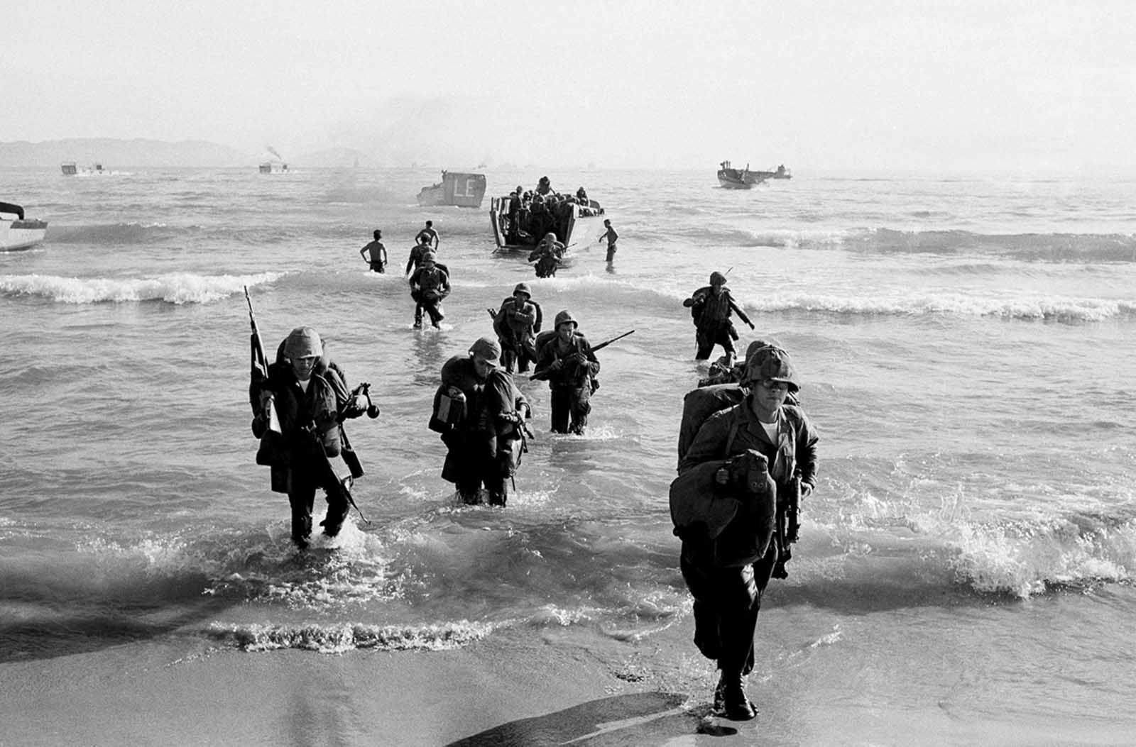 Marines wade ashore with heavy equipment at first light at Red Beach near Da Nang in Saigon on April 10, 1965.
