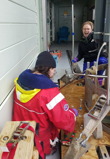 Photo of a woman wearing a warm hat and red jacket, kneeling beside a 6-7 foot tall CTD on the deck of a ship. She is facing away from the camera but can be seen holding a small glass bottle with a syringe stuck into the top. In the background, partially hidden by the CTD, is a young woman mid-laugh, holding a differently shaped glass bottle with a stopper.