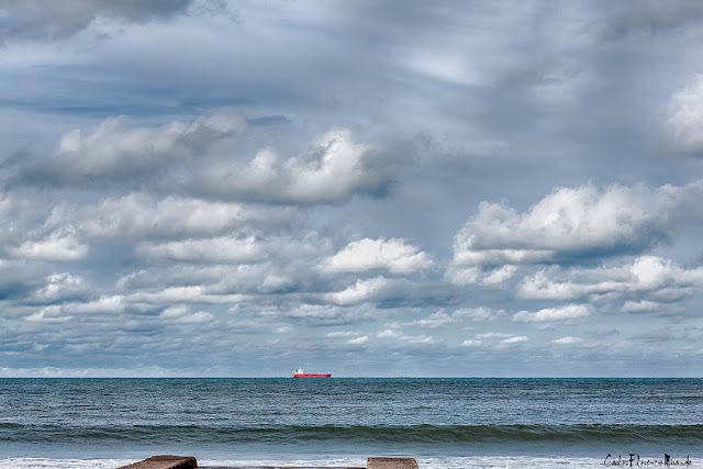 Paisaje nuboso con barco rojo en el horizonte.