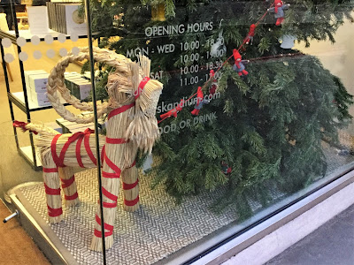 Pic of straw goat with red binding against nearly bare Christmas tree in store window