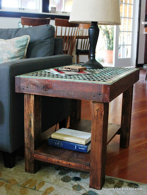 a shelf is added to a side table for extra storage