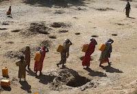 Women carry jerry cans of water from shallow wells dug from the sand along the Shabelle River bed, which is dry due to drought in Somalia's Shabelle region (Credit: news.trust.org) Click to Enlarge.