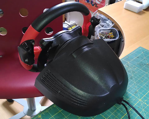 Rear view of steering wheel, with two black Xbox 360 triggers cut from an original joypad controller fixed to the steering wheel.