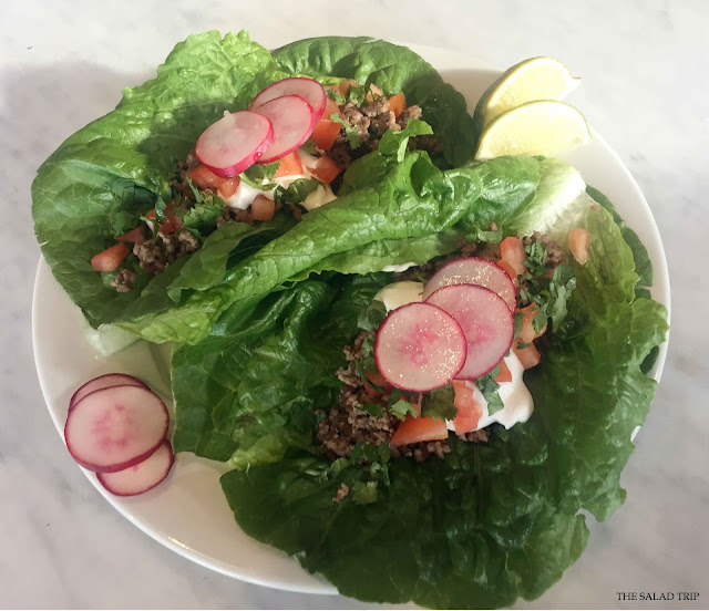 Lettuce leaves filled with taco filling on a white plate and garnished with lime.