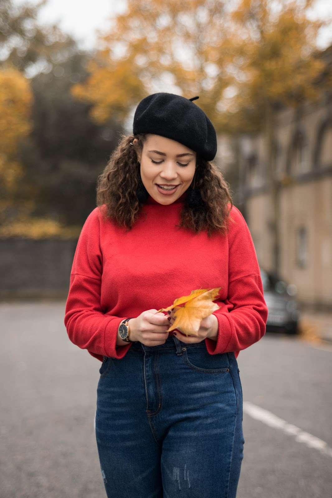 Eboni holding an autumnal leaf in a black beret and red jumper
