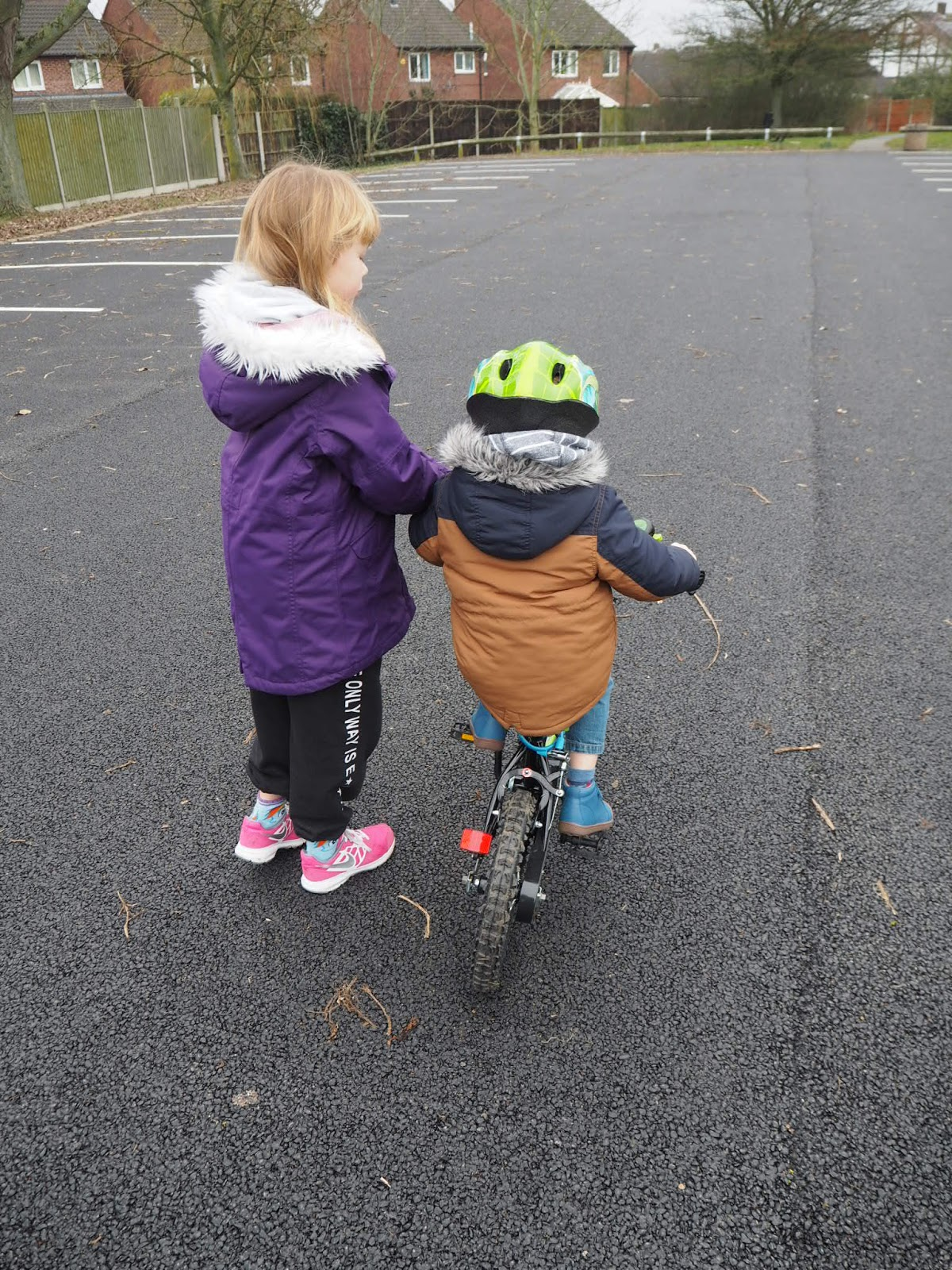Sister helping brother with bike