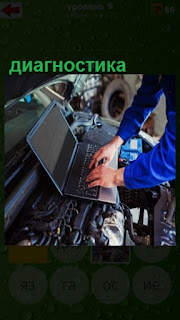мастер делает диагностику автомобиля на ноутбуке