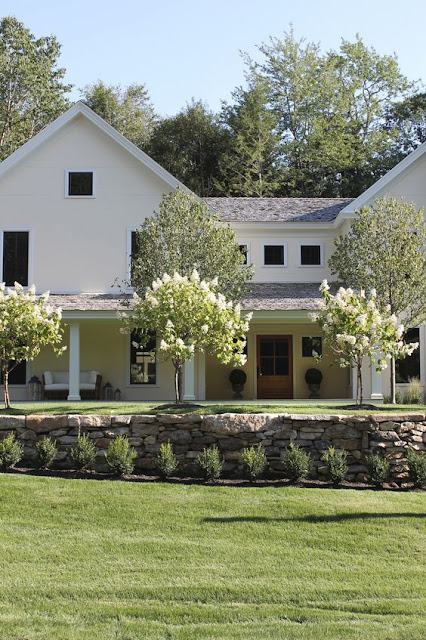 Beautiful modern farmhouse exterior inspiration with front porch, stone wall, and trees