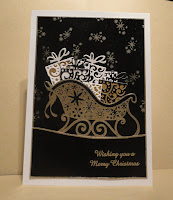 "Black card with image of gold sleigh filled with presents, ""wishing you a merry christmas"" sentiment"