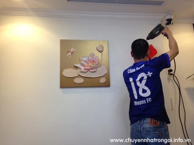 thợ treo tranh ảnh lên tường
