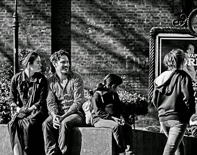 Pareja sentada en plaza mirando gente pasar
