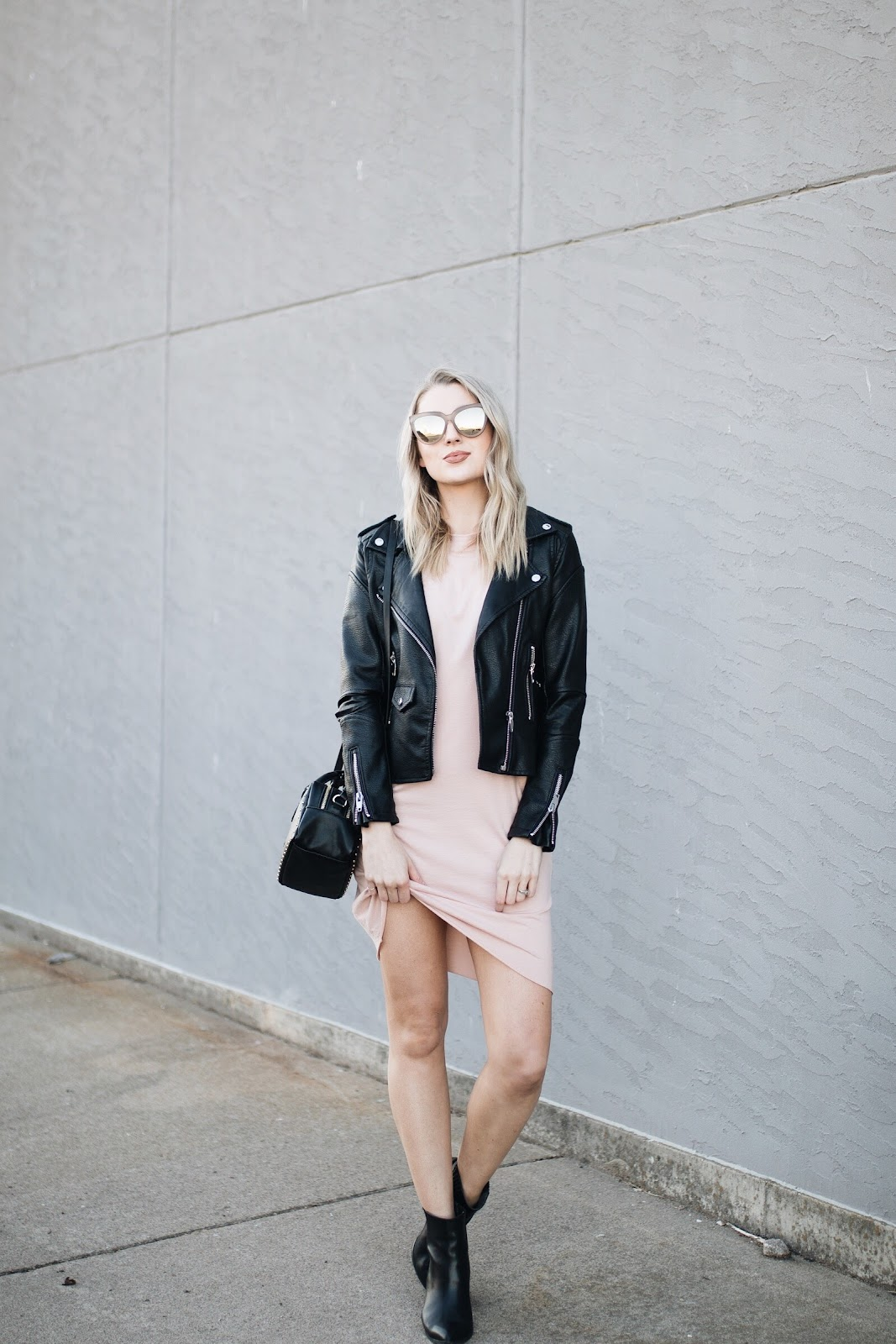 Cute spring transition outfit - t-shirt dress with a leather jacket and ankle boots
