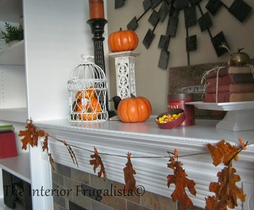 Waxed leaf garland, a bird cage filled with mini pumpkins & gourds, a stack of old books wrapped in twine, candy corn, and a DIY Fall Harvest sign.