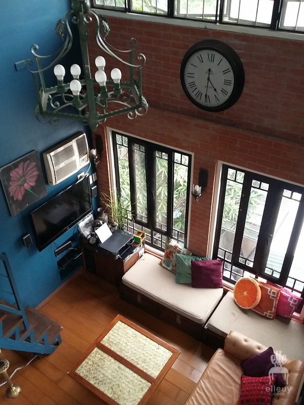 Brick walls, loft living room, high ceiling, wall of windows, vintage living room, wrought iron chandelier, navy blue walls