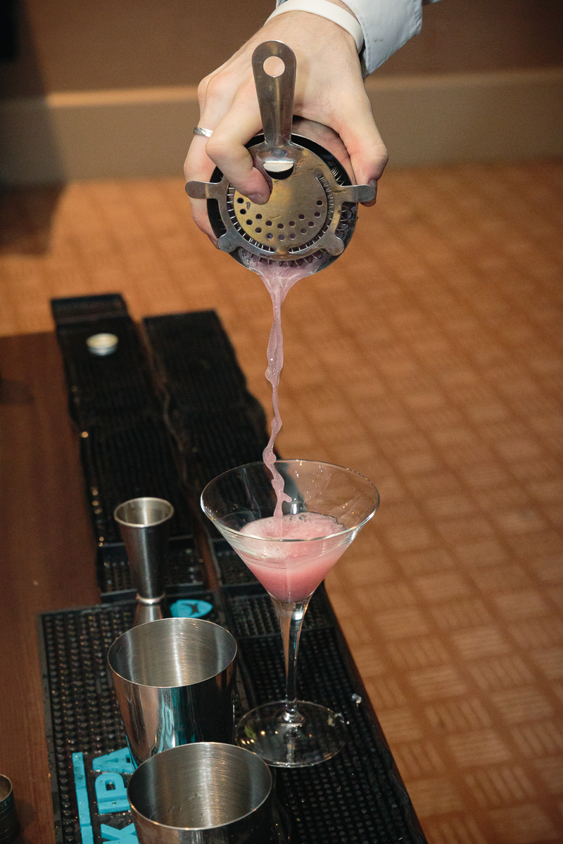 straining cocktail into martini glass