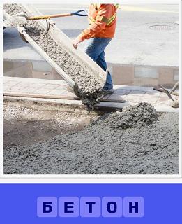 рабочий выливает бетон на дорогу, помогая лопатой