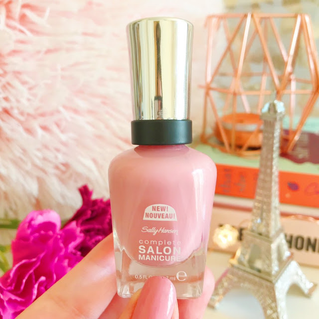 Holding up Sally Hansen Rose To The Occasion Nail Polish. Background of stack of books with copper candle holder on top, eiffel tower statue in front, pink fluffy pillow in left hand side