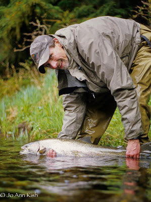 Angler with fly caught steelhead in Southeast Alaska