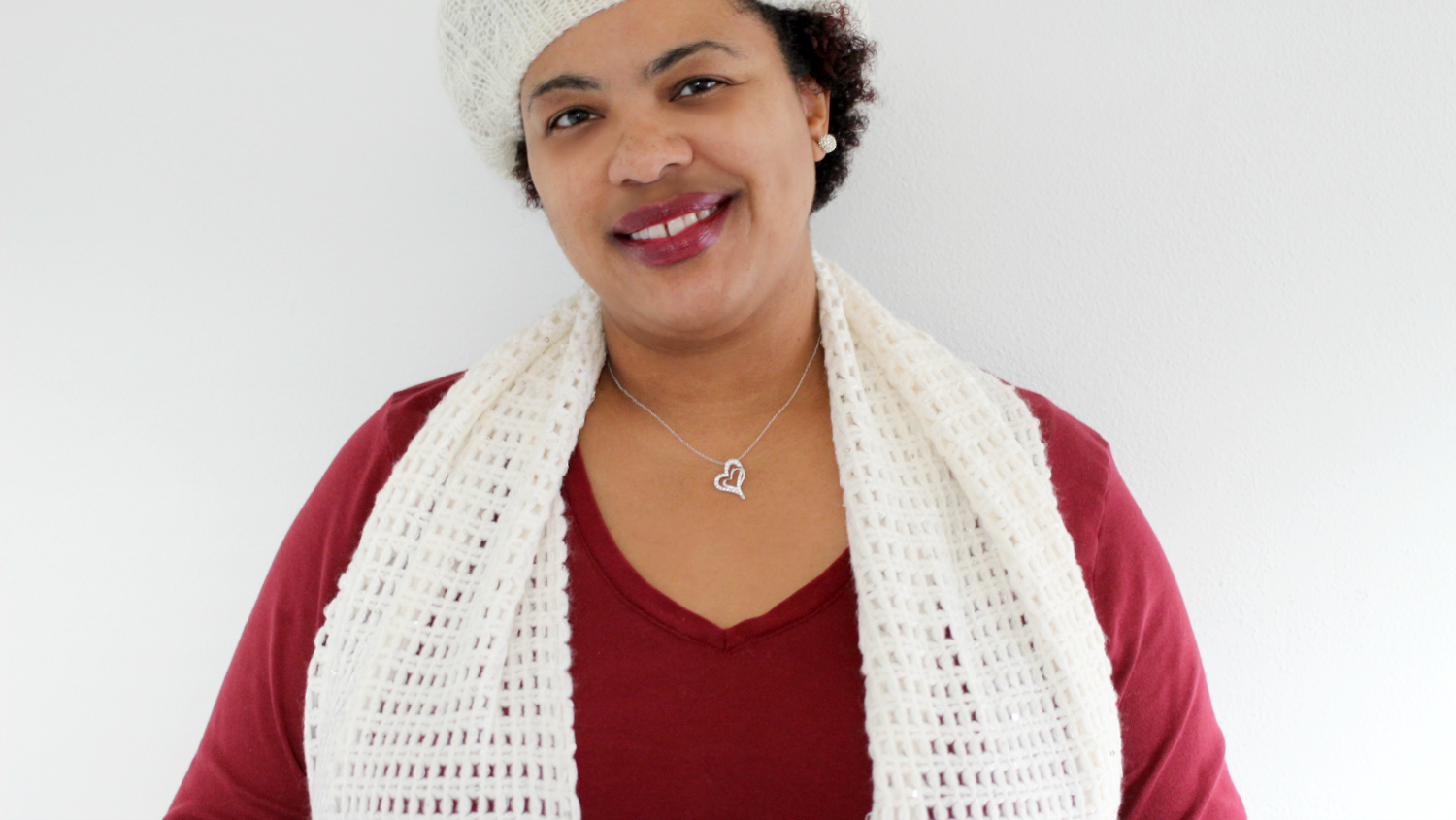 a black women wearing a diamond heart necklace