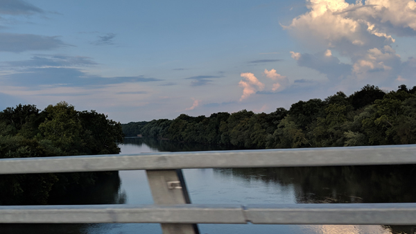 image of the river, lined by thick trees, below a blue sky with pink-lit clouds, seen beyond a set of guardrails