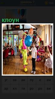 в помещении клоун с шариками играет с детьми
