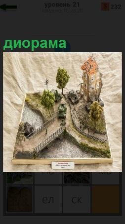 На доске сделан макет диорамы с танками, людьми и деревьями