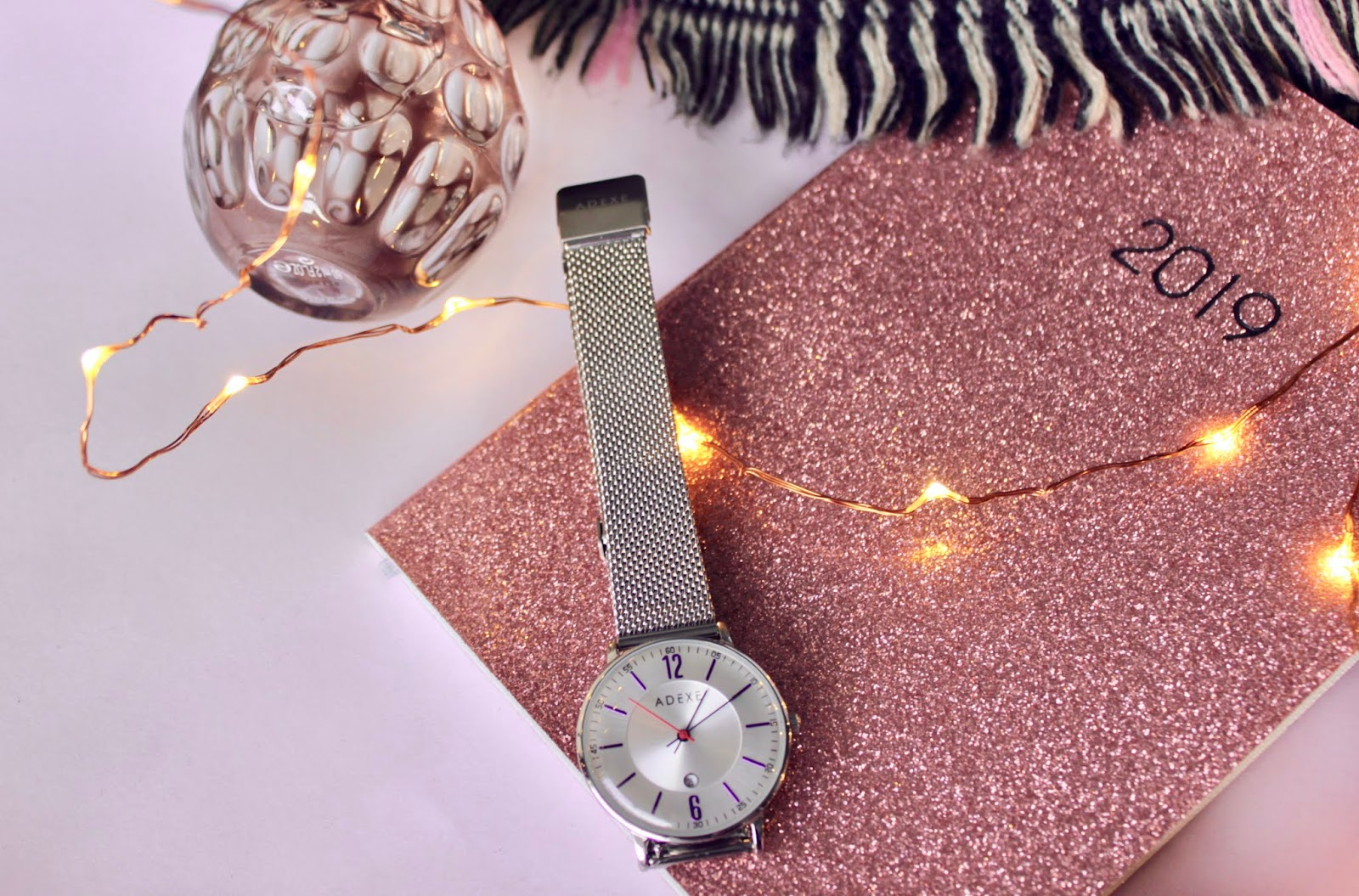 A silver ADEXE watch with some fairy lights and sparkle
