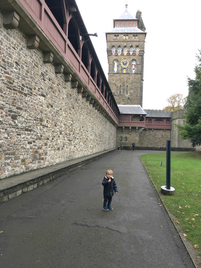 toddler-stood-in-front-of-clock-tower-at-cardiff-castle