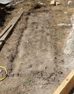 A shallow trench prepared for the raised bed