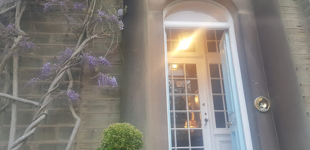 The front door of Sunnybank Guesthouse draped in light purple flowers.