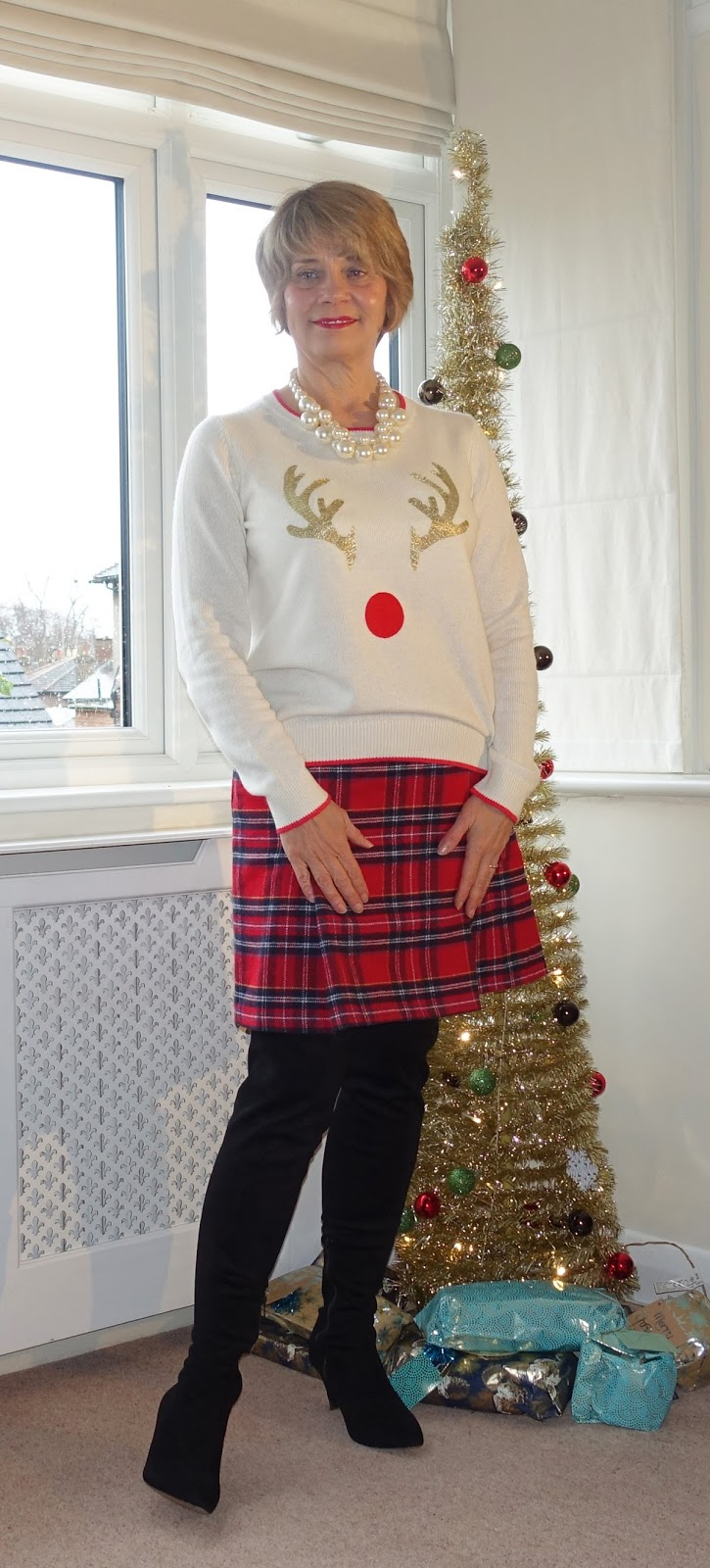Image showing a 50 plus woman posing by a Christmas tree wearing a Christmas jumper and red tartan skirt