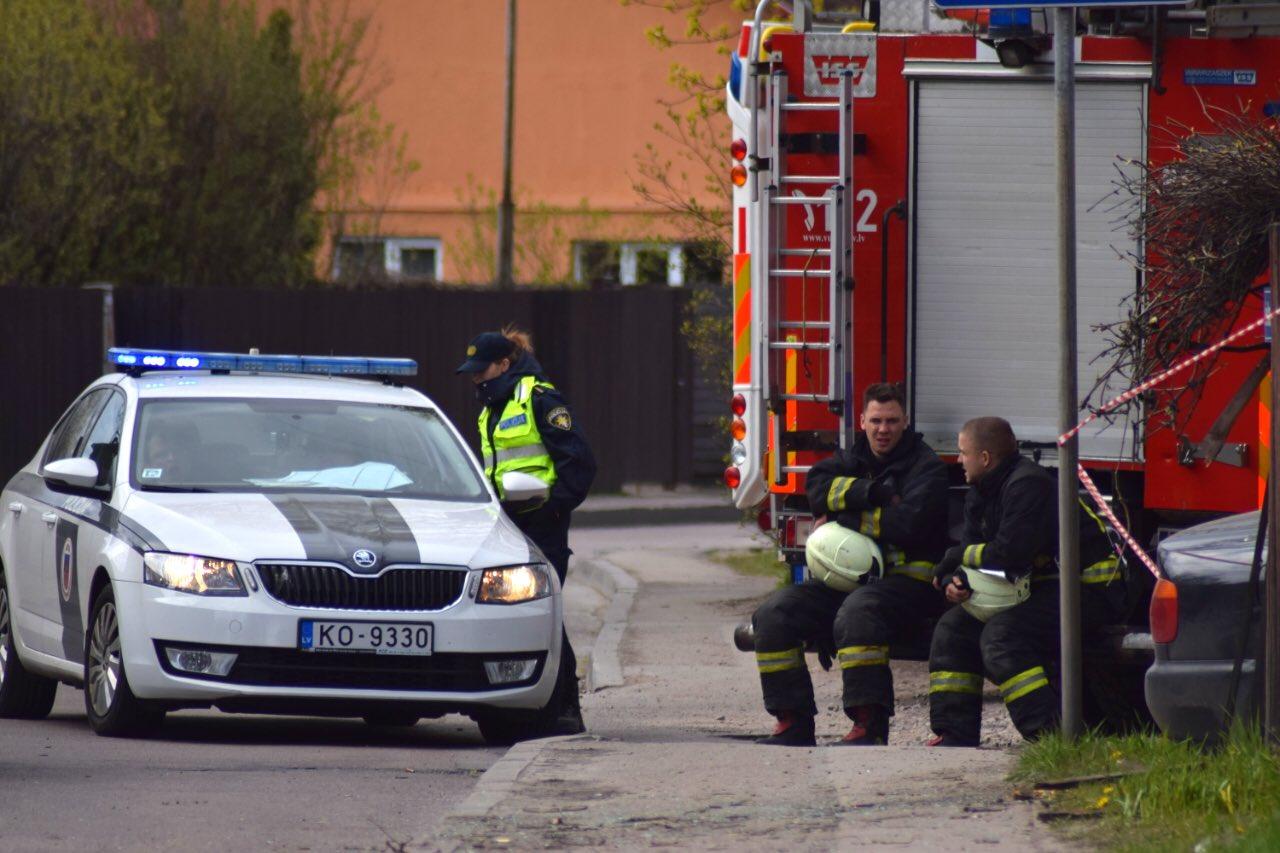 Ugunsdzēsēji un policiste pie mašīnām