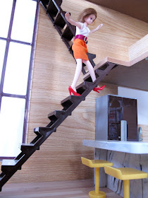 A doll teetering at the top of the stairs of the modern Lori Loft to Love dolls' house.