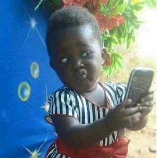 a small girl checking herself on a mirror