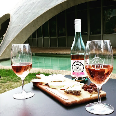 Two glasses of rose, with the bottle they came from (and a cheese board) on a table in front of The Shine Dome.