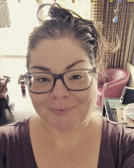 image of me from the shoulders up in the morning sunlight in my dining room; I'm wearing a pink henley top and grey-framed glasses, with my hair up in a messy bun