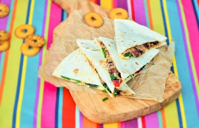 Bean, Spinach and Red Pepper Quesadillas stacked on a colourful mexican stripy napkin
