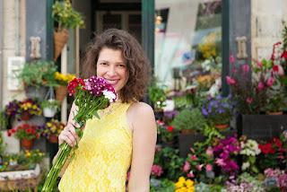 pessoa com flores na mão e muitas flores atrás, na porta da floricultura