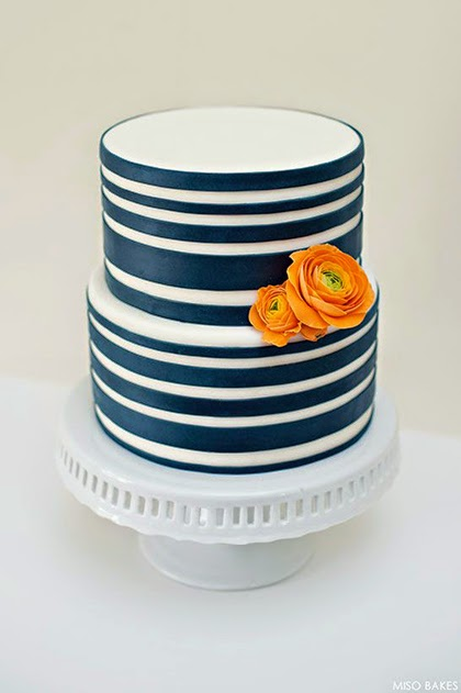 Navy blue striped cake with orange sugar paste Ranunculus by Miso Bakes.